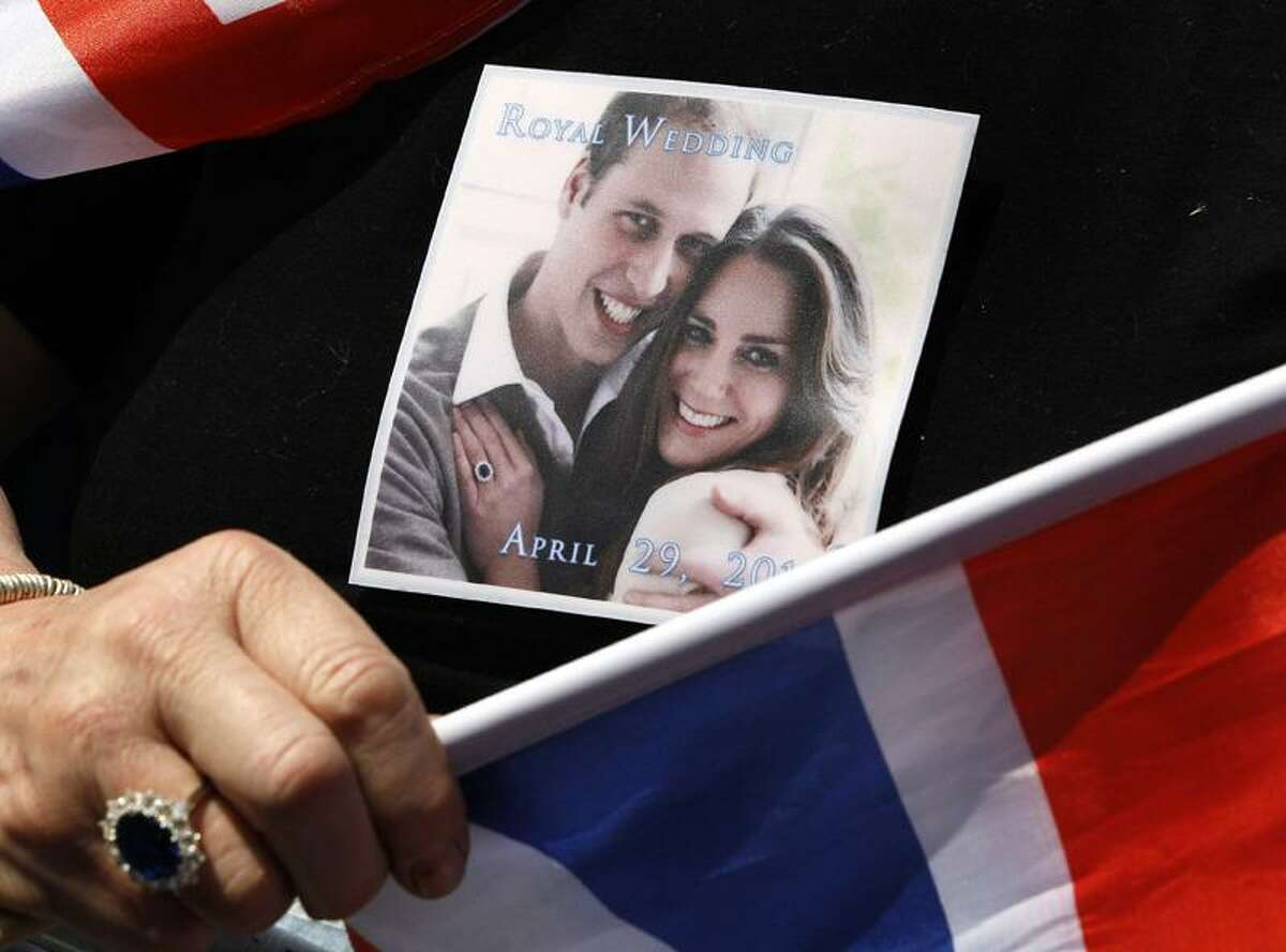 A picture of Prince William and Kate Middleton is seen on a T-shirt, and a ring similar to that of Kate Middleton's engagement ring worn by a royal fan waiting near Westminster Abbey in London Thursday. Associated Press