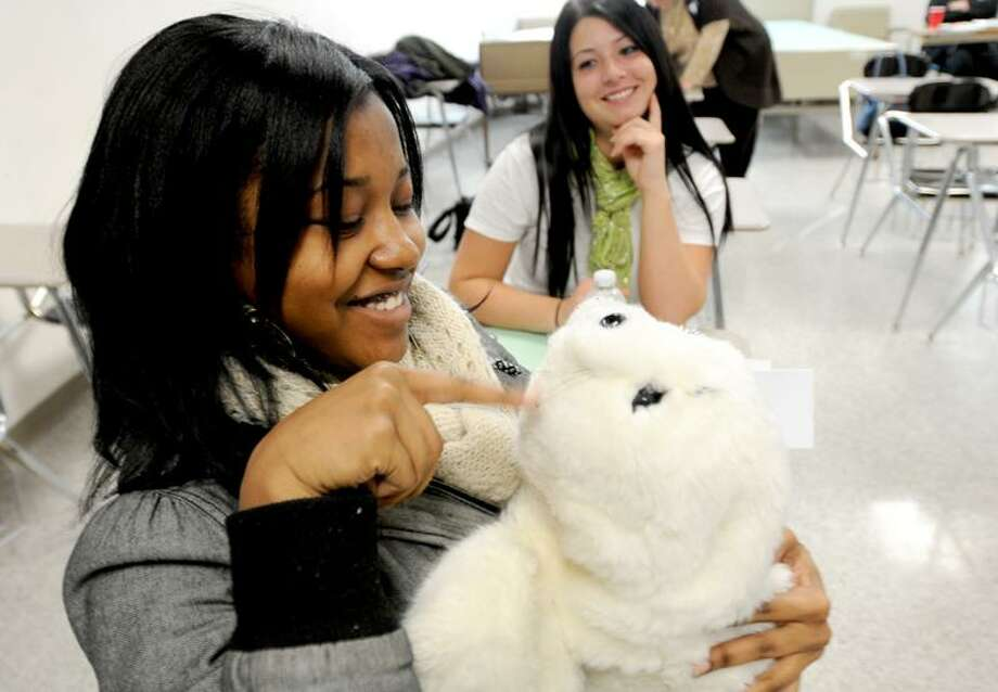 Angel Elder of Hamden High School admires Paro, a $6,000 therapeutic robot used for pet therapy. The robot was brought to school by guest speaker Jason Barcomb, director of therapeutic recreation at the Hamden Health Care Center, for a nursing assistant program that also prepares students in dementia care. Peter Hvizdak/Register