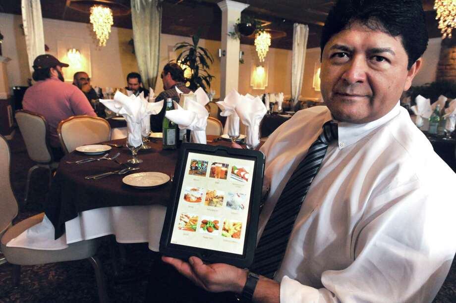 LaLuna Ristorante owner Edgar Ortiz holds one of the tablets the Branford restaurant is using to display its menu. (Photo by VM Williams/Register)