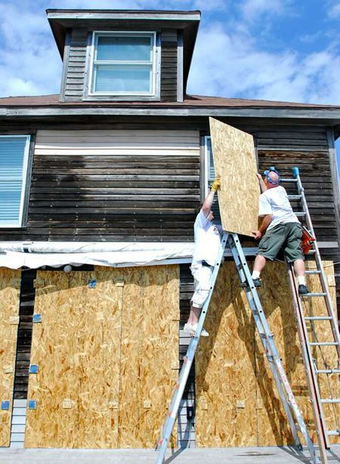 Frank Odice (right) and Scott Brewer (far right) of Affordable Handyman of Connecticut board up windows with plywood in the back of a home on East Broadway in Milford on Friday 8/26/2011. The home is located on the beach next to Silver Sands State Park and faces the Long Island Sound. Photo by Arnold Gold/New Haven Register