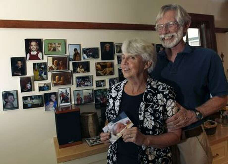 AP PhotoEileen and Doug Flockhart laugh as she holds a picture of their seventh grandchild near a wall full of family photos in their home in Exeter, N.H., Wednesday, Aug. 24, 2011. America is swiftly becoming a granny state. Less frail and more engaged, today's grandparents are shunning retirement homes and stepping in more than ever to raise grandchildren while young adults struggle in the poor economy. Now making up 1 in 4 adults, grandparents are growing in numbers at twice the rate of the overall population, staying in the work force and sticking close to families, according to new census figures. Photo: ASSOCIATED PRESS / AP2011