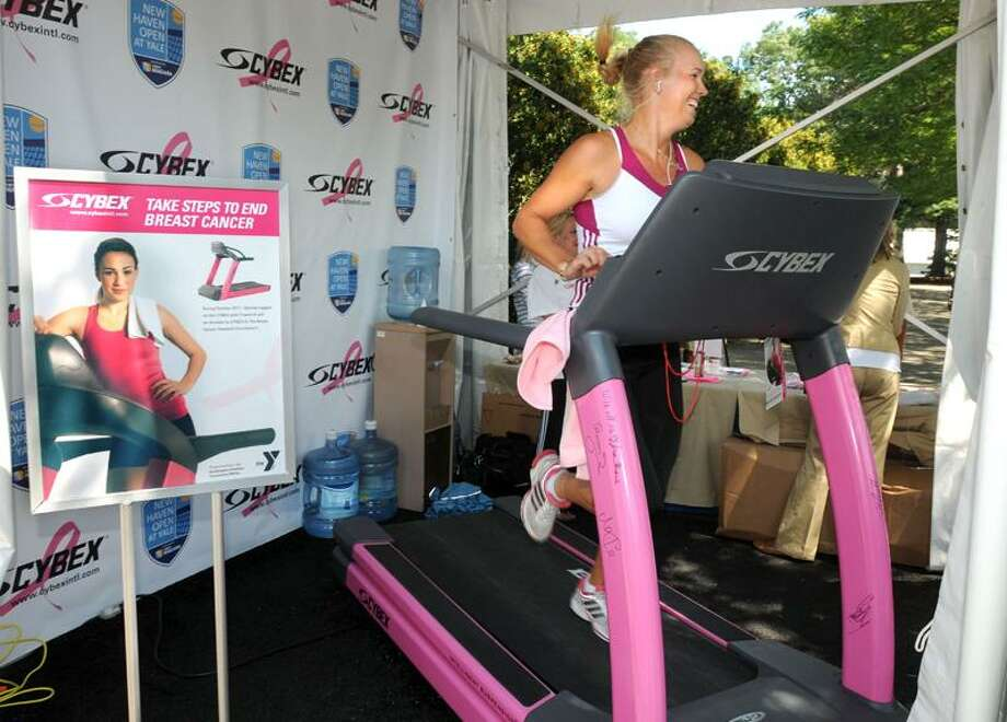 Caroline Wozniacki runs on the Cybex Pink Ribbon treadmill at the Cybex booth at the New Haven Open at Yale to help raise money for breast cancer research. (Mara Lavitt/Register)  8/24/11