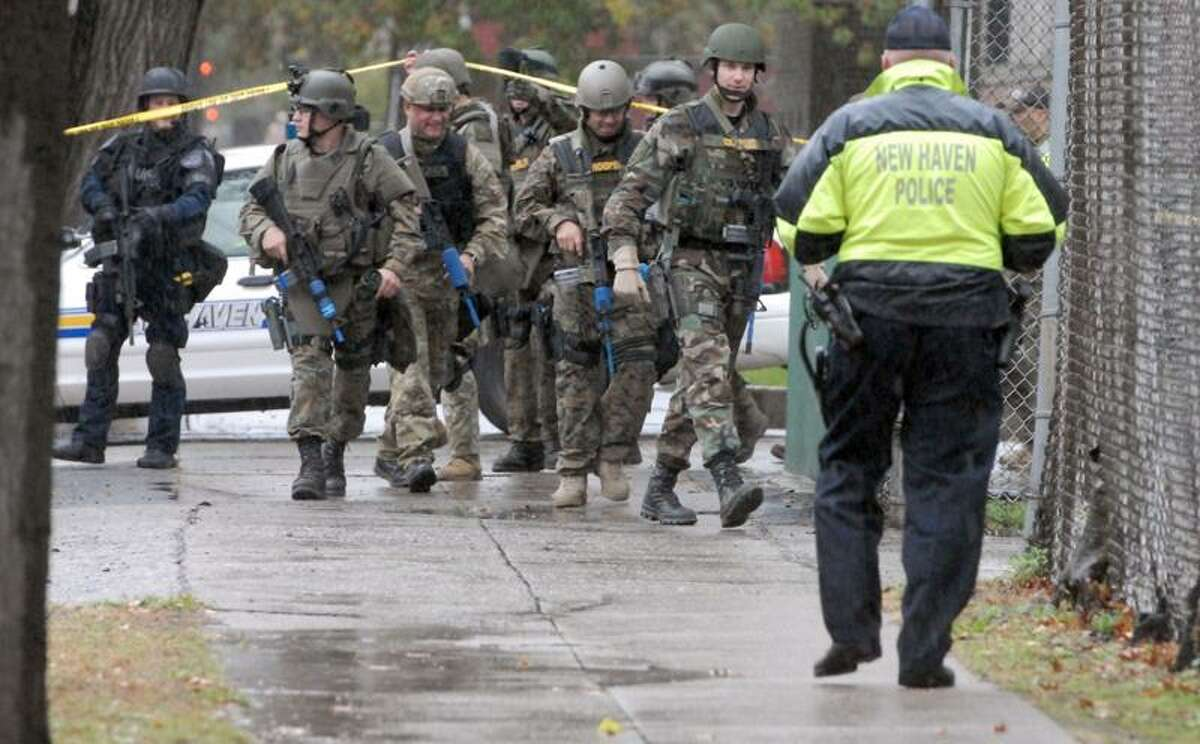 State Police SWAT team members that had been training nearby pass the police investigation scene on Shelton Avenue Thursday in New Haven. Mara Lavitt/Register
