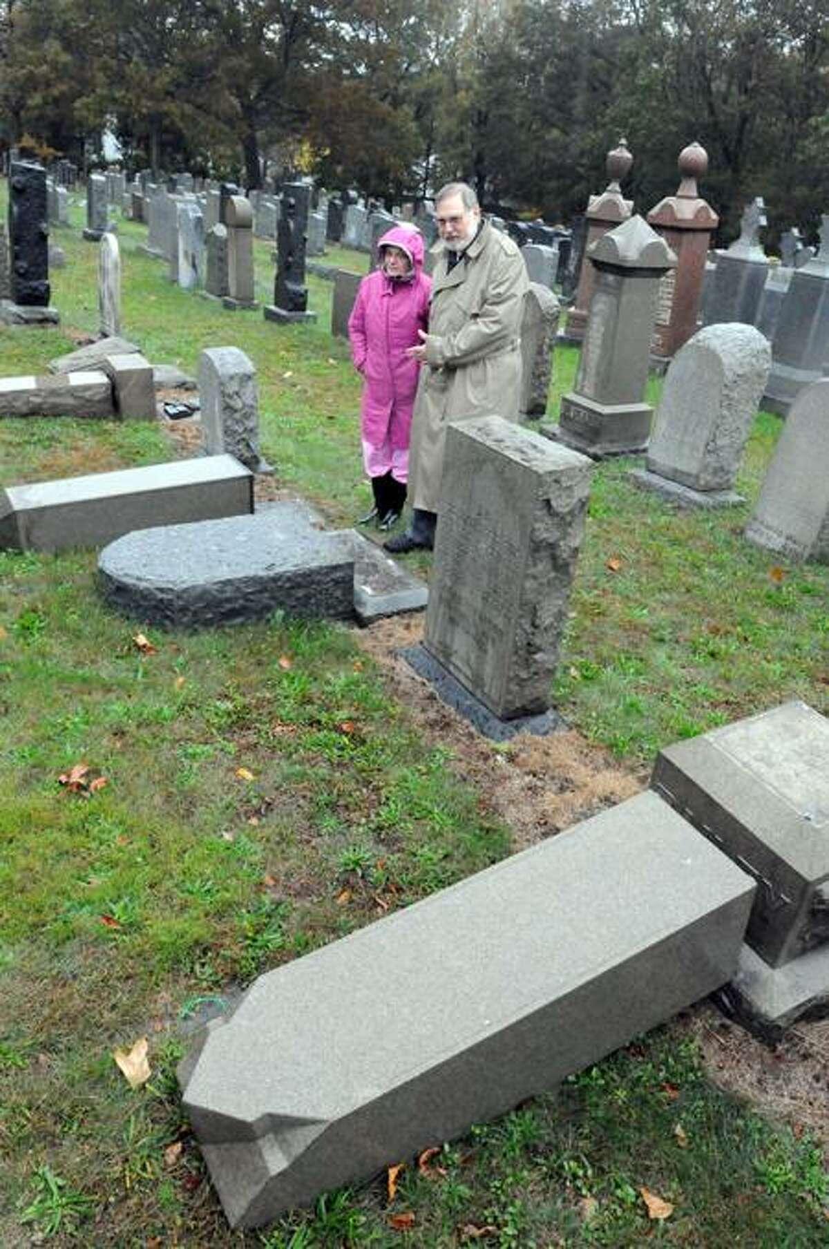 Goldie Goldberg, left, co-chairwoman of the Bikur Cholim Sheveth Achim Cemetery Committee, and congregation President Len Honeyman examine vandalism at the East Haven cemetery Thursday. Peter Hvizdak/Register