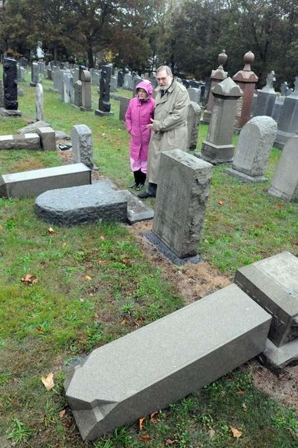 Goldie Goldberg, left, co-chairwoman of the Bikur Cholim Sheveth Achim Cemetery Committee, and congregation President Len Honeyman examine vandalism at the East Haven cemetery Thursday. Peter Hvizdak/Register / PETER HVIZDAK