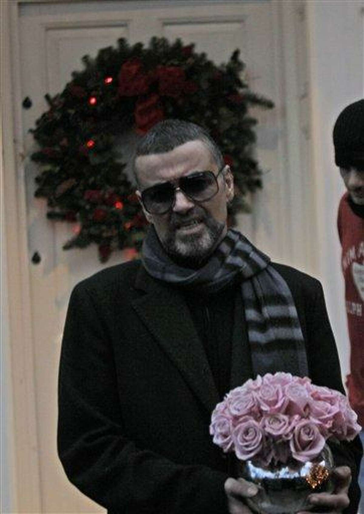 British singer George Michael talks to reporters outside his house in north London, Friday. Michael, short of breath and appearing weak, said he has recovered from a life-threatening bout of pneumonia. Associated Press