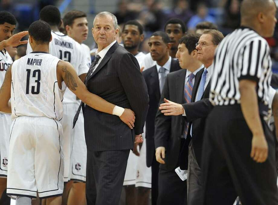 Connecticut head coach Jim Calhoun, second from left, is held back by Connecticut's Shabazz Napier (13) during a timeout in the first half of an NCAA college basketball game against Fairfield in Hartford, Conn., Thursday, Dec. 22, 2011.  (AP Photo/Jessica Hill) Photo: AP / AP2011