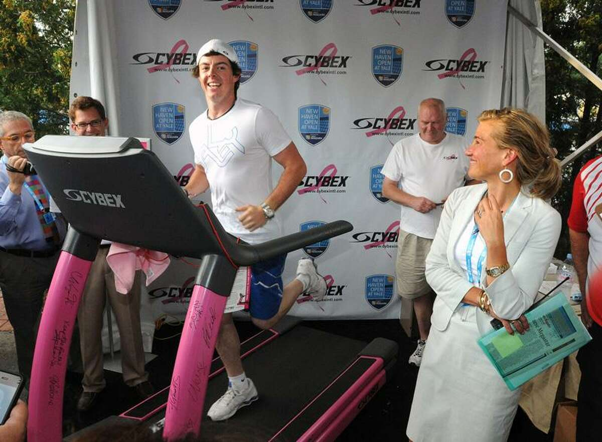 New Haven-- US Open champion Rory McIlroy runs a mile in the Cybex Pink Ribbon Run at NHO. On the right is the tournament director Anne Worcester Photo-Peter Casolino/New Haven RegisterCas110825 8/25/11