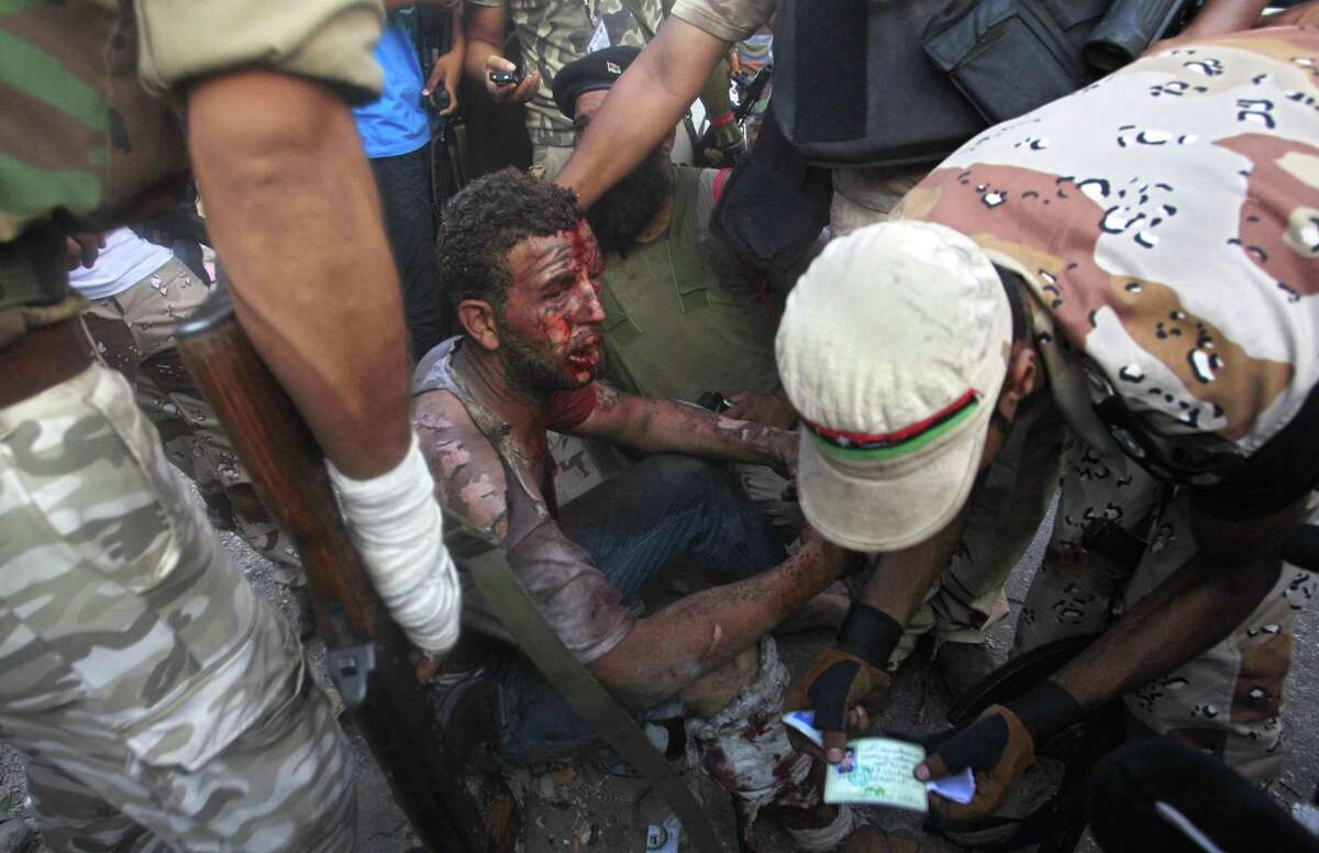 Rebel fighters check the ID of captured loyalist soldier during street fighting in the Abu Salim district in Tripoli Thursday. Associated Press
