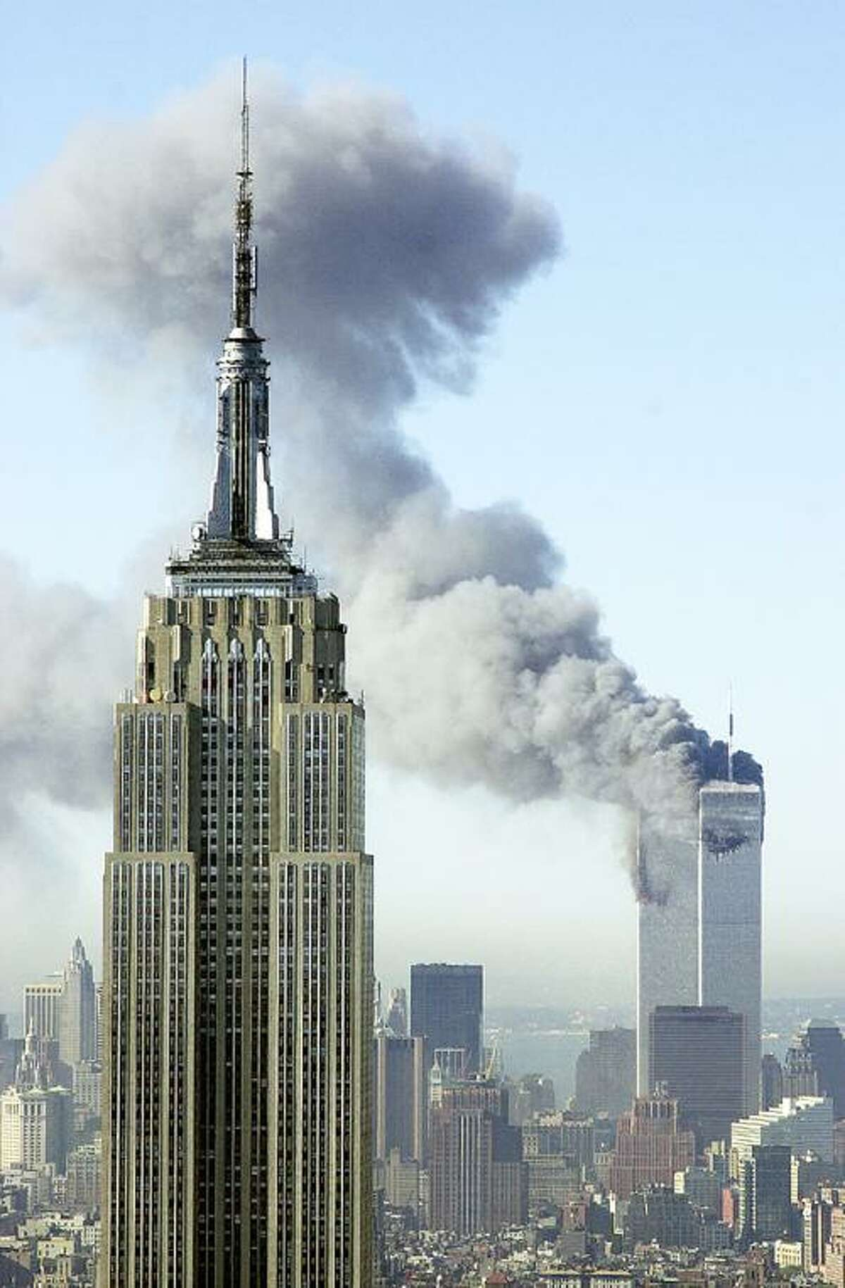In this Sept. 11, 2001, file photo, plumes of smoke rise from the World Trade Center buildings in New York. The Empire State building is seen in the foreground. Television viewers who want to immerse themselves in memories of the Sept. 11 terrorist attacks as the 10th anniversary approaches will have a staggering number of choices, and on the day itself, broadcast and cable news networks will all have their top talent on hand for special coverage. (AP Photo/Patrick Sison, File)