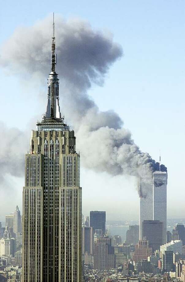 In this Sept. 11, 2001, file photo, plumes of smoke rise from the World Trade Center buildings in New York. The Empire State building is seen in the foreground. Television viewers who want to immerse themselves in memories of the Sept. 11 terrorist attacks as the 10th anniversary approaches will have a staggering number of choices, and on the day itself, broadcast and cable news networks will all have their top talent on hand for special coverage. (AP Photo/Patrick Sison, File) Photo: ASSOCIATED PRESS / AP2001