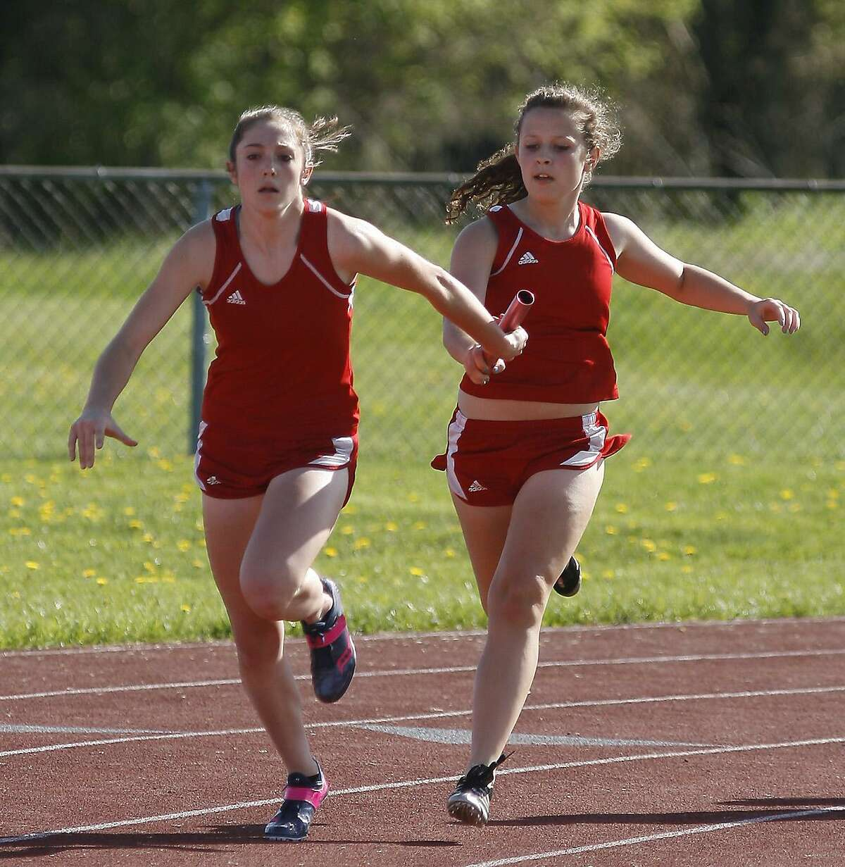 Dispatch Staff Photo by JOHN HAEGER VVS Alexis Kavanaugh takes the handoff from Kayla Prentice for the final leg of the 4x100 relay on Wednesday, May 11, 2011 in a meet against Oneida and UND at VVS. The Red Devils pulled out of the Tri-Valley League on Wednesday, August 24, 2011.