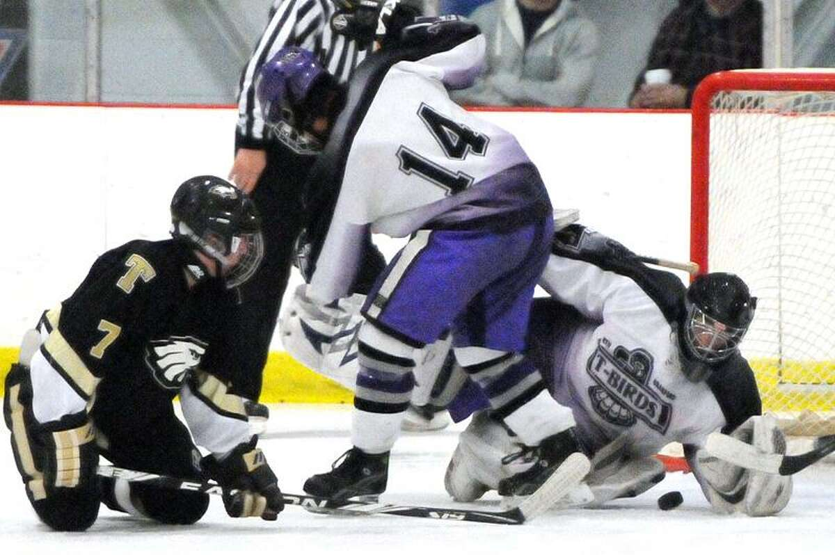 Goalie Kyle Saroka of North Branford High School makes a save as teammate Sam Amendola helps defend the goal against Trumbull High School during second period hockey action Friday 12/23/11 at the Northford Ice Pavilion. Photo by Peter Hvizdak / New Haven Register December 23, 2011 ph2430 Connecticut