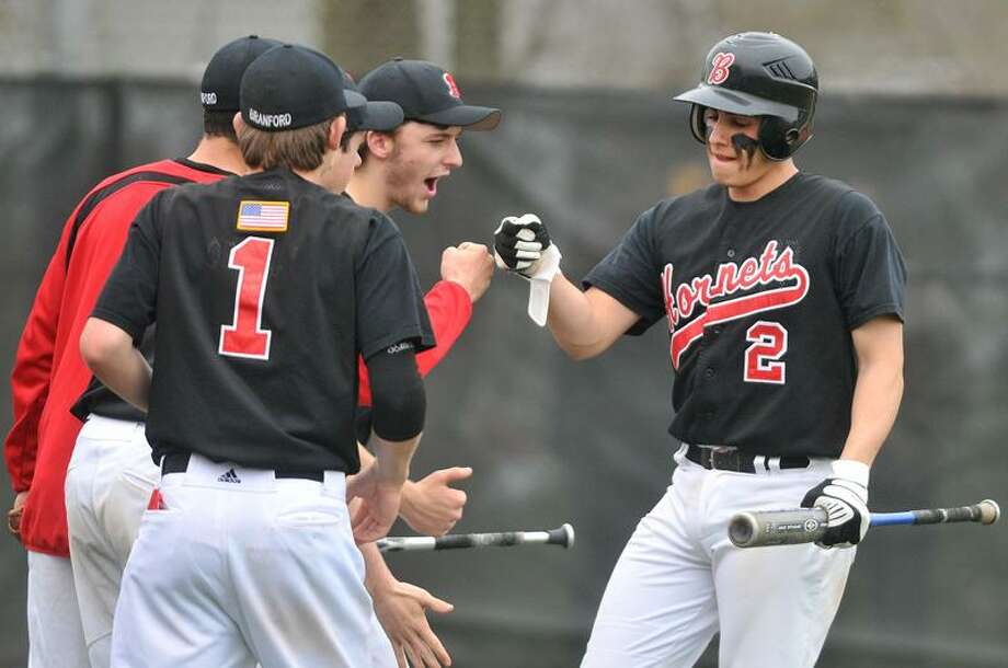 Branford's Buddy Shea is greeted by teammates after crossing home plate in Wednesday's win over North Haven.   Photo by Brad Horrigan/New Haven Register
