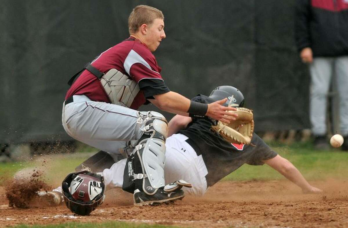 Branford's Jeff Stoddard slides into home plate ahead of the throw made to North Haven catcher Matt Oestrecher. Photo by Brad Horrigan/New Haven Register