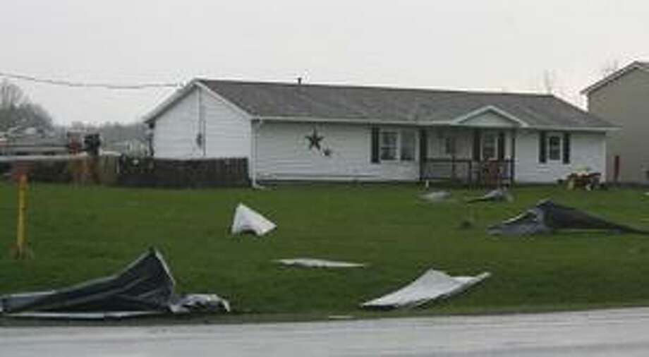 Photo by JOHN HAEGER Part of a roof lies on a lawn in the Town of Lenox after a storm Tuesday, April 26, 2011.