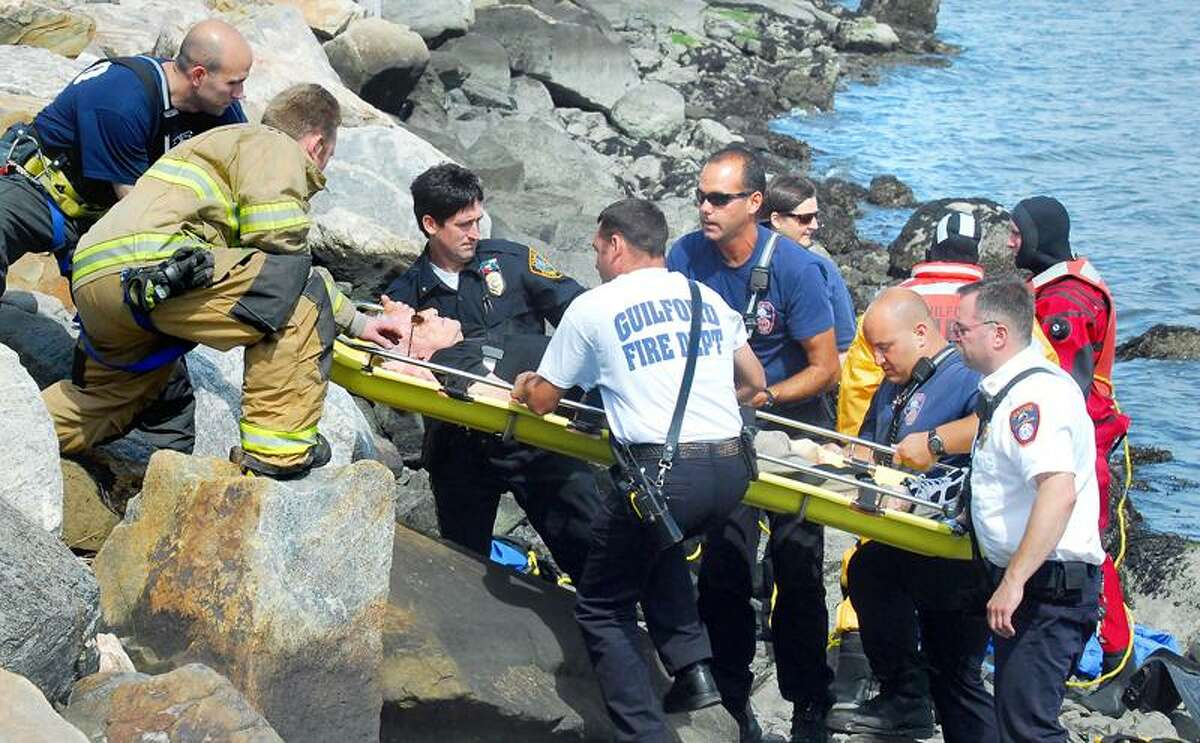 Guilford emergency personnel lift an elderly man up an embankment at the Guilford Town Dock parking lot on Wednesday afternoon 8/24/2011. He had driven his Audi into the water and was rescued by Dennis Buckley (not in photo) of Bridgeport. Photo by Arnold Gold/New Haven Register