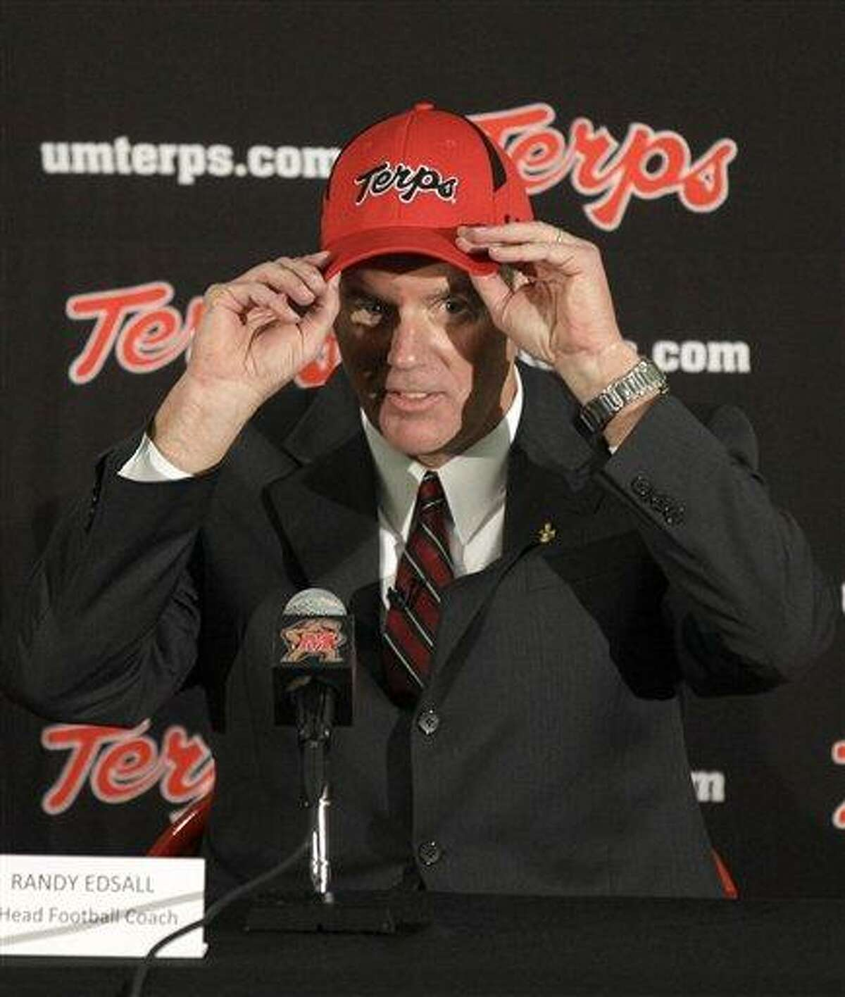 Randy Edsall puts on a University of Maryland hat after being introduced as the new head football coach at the school during a news conference, Monday, Jan. 3, 2011, in College Park, Md. (AP Photo/Rob Carr)