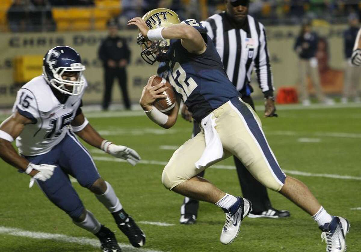 Pittsburgh quarterback Tino Sunseri (12) scrambles past Connecticut safety Jerome Junior (15) and goes in for a touchdown in the first quarter of an NCAA college football game Wednesday, Oct. 26, 2011, in Pittsburgh. (AP Photo/Keith Srakocic)