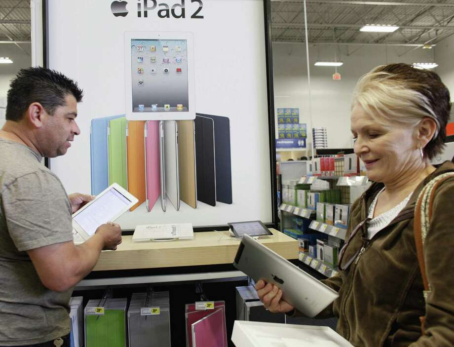 Leticia Lozano, right, shops for a case for her new Apple iPad 2 tablet at Best Buy in Glendale, Calif. on April 6. Americans' concerns about jobs and inflation eased somewhat in April, pushing the Consumer Confidence Index higher. (AP Photo/Damian Dovarganes) Photo: ASSOCIATED PRESS / AP2011