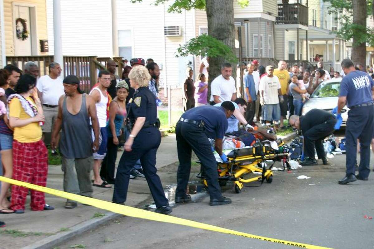 Police and bystanders are seen at the scene of a shooting Wednesday in the Hill neighborhood. William Kaempffer/Register