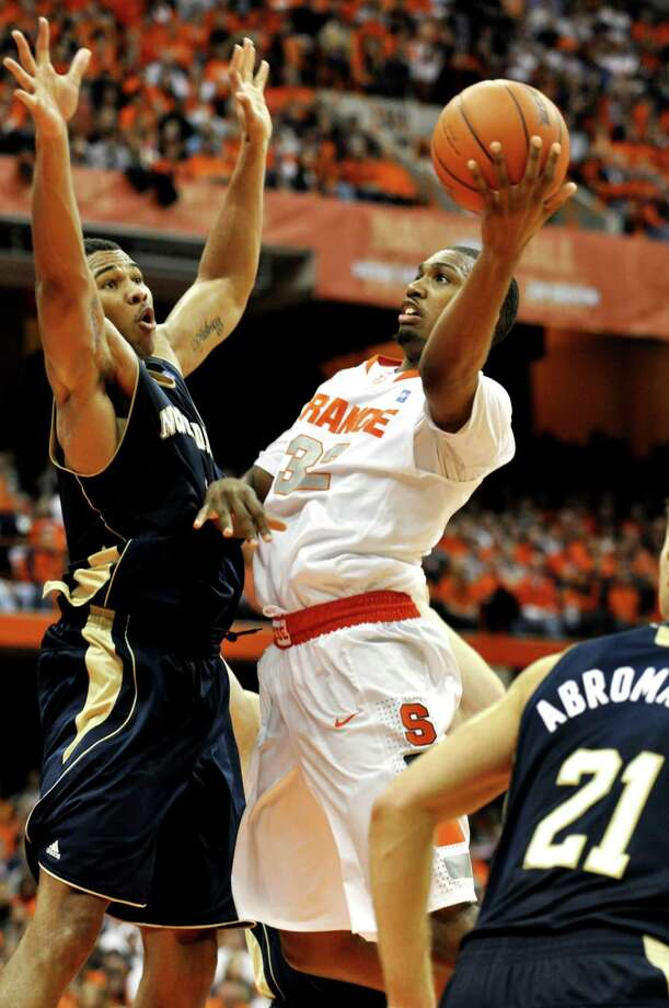 Syracuse's Kris Joseph, right, shoots against Notre Dame's Tyrone Nash during the second half of an NCAA college basketball game in Syracuse, N.Y., Saturday, Jan. 1, 2011. Syracuse won 70-58. (AP Photo/Kevin Rivoli) Photo: AP / FR60349 AP