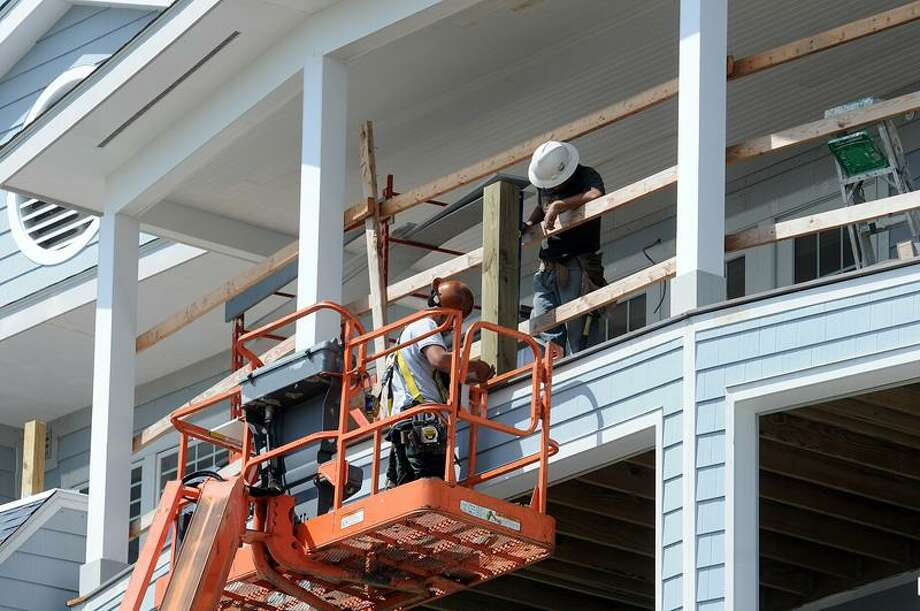 Workers install railings Wednesday on the top balconies at the Madison Beach Hotel.  Peter Casolino/Register