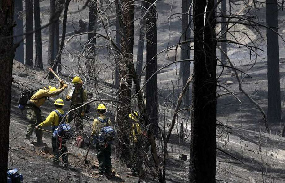 Crews douse hot spots from the wildfire near Los Alamos, N.M. on Friday Associated Press Photo: AP / AP