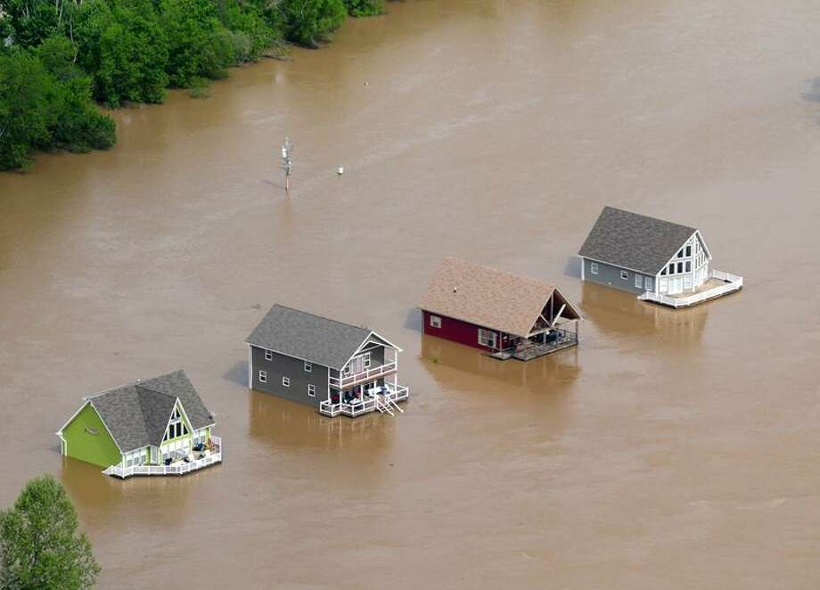 Four houses are surrounded by floodwaters from the Current River just outside Doniphan, Mo., Tuesday. Associated Press Photo: AP / Daily American Republic