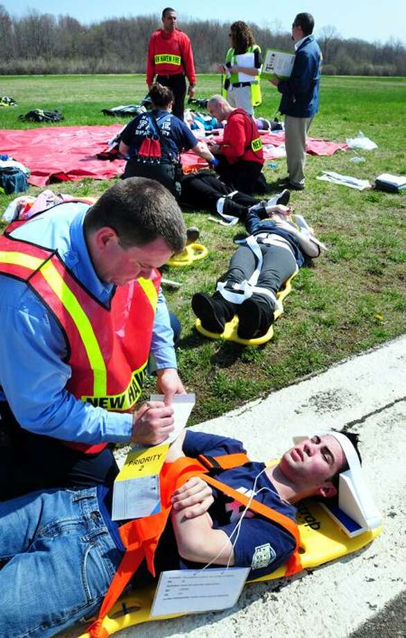 Shaun Connolly. left, of the West Haven Fire Department attends to Michael Brainerd, 16, at Tweed New Haven Regional Airport during a disaster drill Tuesday. Arnold Gold/Register