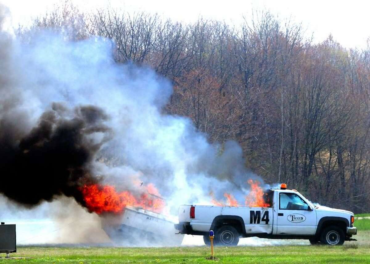 A fire burns following an explosion at the start of Tuesday's disaster drill at Tweed New Haven Regional Airport. Arnold Gold/Register