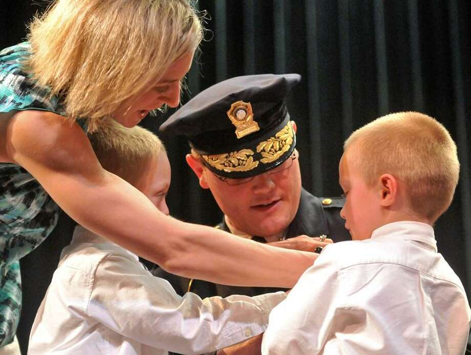 It's a family affair as Alycia Mulhern puts a badge on her husband, Jonathan Mulhern, with the help of their sons, Hayden and Carter. Jonathan Mulhern is now the deputy chief of the North Haven Police Department. Brad Horrigan/Register