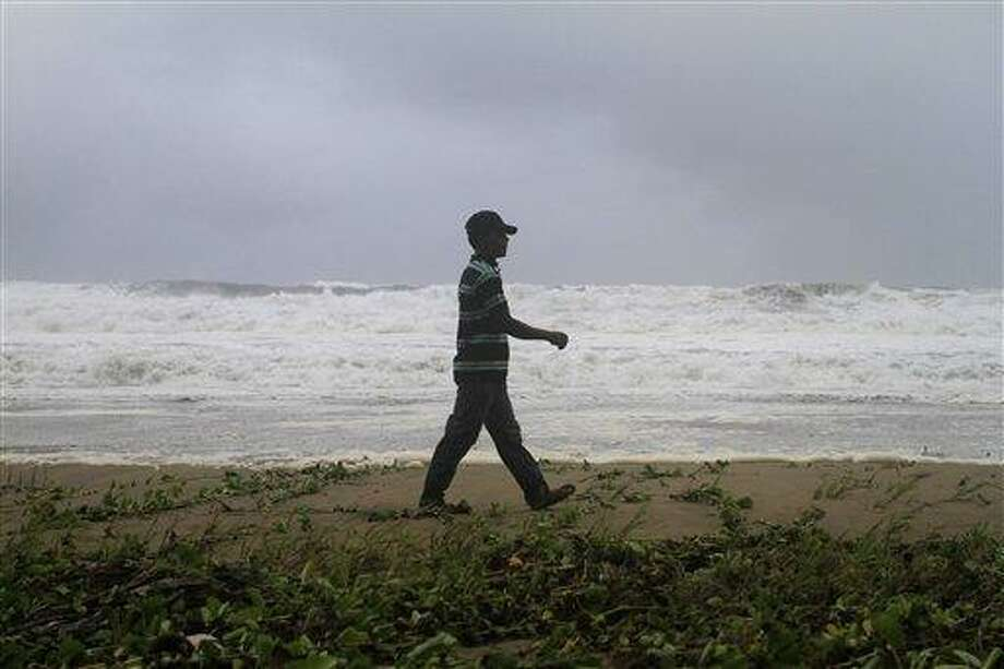 A resident walks along Los Yayales beach as strong waves crash due to the approach of Hurricane Irene to Nagua, in the northern coast of the Dominican Republic, Monday, Aug, 22, 2011. Hurricane Irene churned into a stronger Category 2 storm on Monday evening, after raking Puerto Rico with strong winds and rain that knocked out power to more than a million people, on a track that could carry it to the U.S. Southeast as a major storm by the end of the week. (AP Photo/Roberto Guzman) Photo: AP / AP