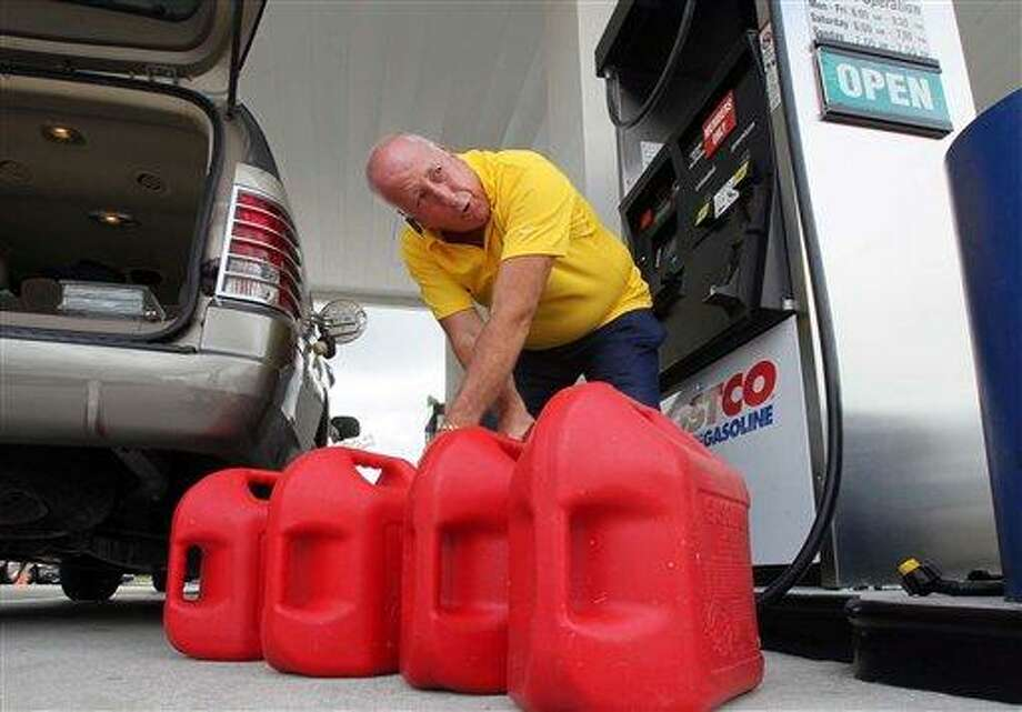 Jay Coleman fills up spare gasoline containers at Costco in preparation for Hurricane Irene, Monday, Aug. 22, 2011, in Royal Palm Beach, Fla. The U.S. National Hurricane Center projected that Irene could grow into a Category 3 hurricane with winds of 115 mph (184 kph) over the Bahamas on Thursday. And it may carry that force northwest along Florida's Atlantic coast and toward a possible strike on South Carolina, though the forecasters warned that by the weekend, the storm's path could vary significantly from the current projection. (AP Photo/The Palm Beach Post, Allen Eyestone) MAGS OUT; TV OUT; NO SALES Photo: AP / The Palm Beach Post