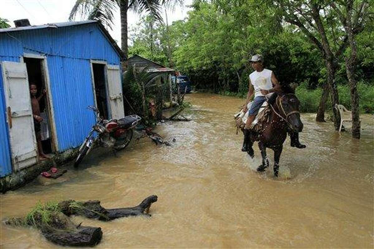 A resident rides a horse through a flooded neighborhood after the passing of Hurricane Irene in Nagua on the northern coast of the Dominican Republic, Tuesday Aug. 23, 2011. Hundreds were displaced by flooding in the Dominican Republic, forced to take refuge in churches, schools or relatives' homes. Electricity also was cut in some areas. (AP Photo/Roberto Guzman)