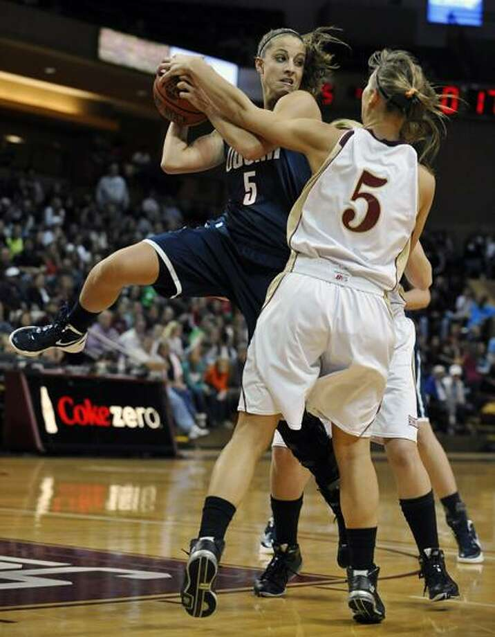 Connecticut's Caroline Doty, left, looks to pass as College of Charleston's Cathryn Hardy defends during the first half of an NCAA college basketball game on Wednesday, Dec. 21, 2011, in Charleston, S.C.  (AP Photo/Rainier Ehrhardt) Photo: AP / FR155191 AP
