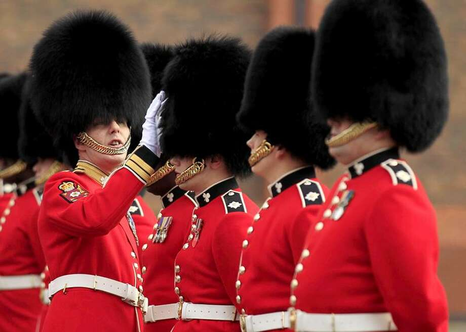 A Company Sergeant Major of the 1st Battalion Irish Guards inspects guardsmen's bearskins, as they take part in an inspection ahead of the royal wedding at their barracks in Windsor, England, Thursday, April 21, 2011.  Britain's Prince William is due to marry Kate Middleton on April 29.  (AP Photo/Matt Dunham) Photo: ASSOCIATED PRESS / AP2011