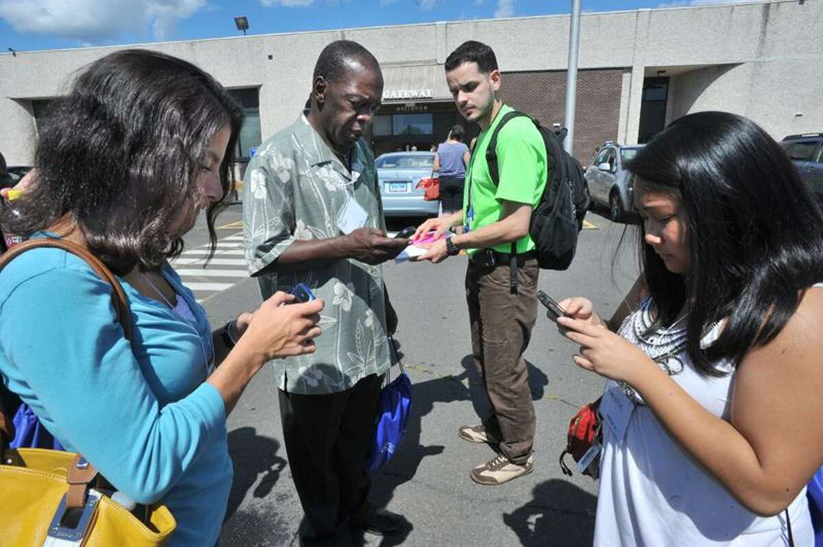 Gateway Community College students text friends and family after being evacuated from the building because of earthquake tremors. Melanie Stengel/Register