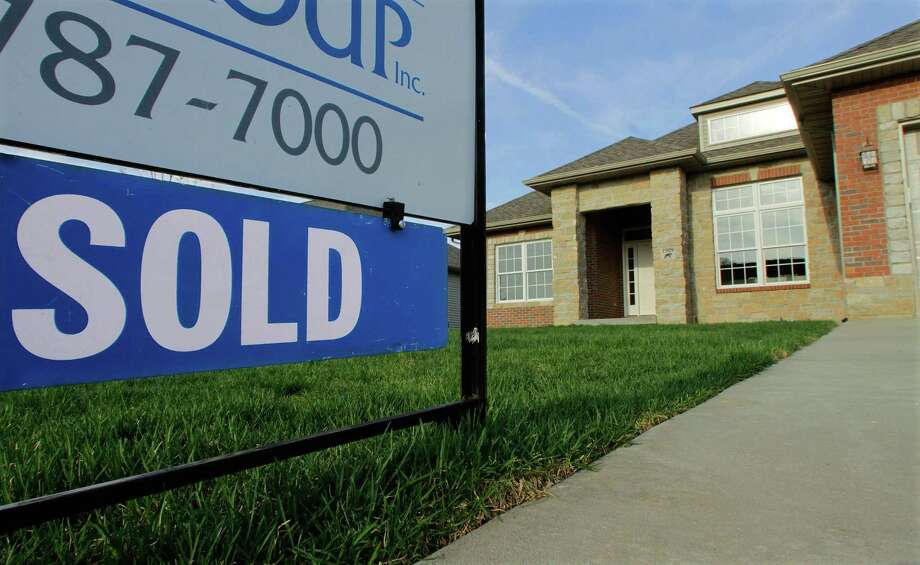 In this photo taken April 18, a sold sign is seen on a recently built new residential home in Illinois. More people bought new homes in March, according to a report out Monday.(AP Photo/Seth Perlman) Photo: ASSOCIATED PRESS / AP2011