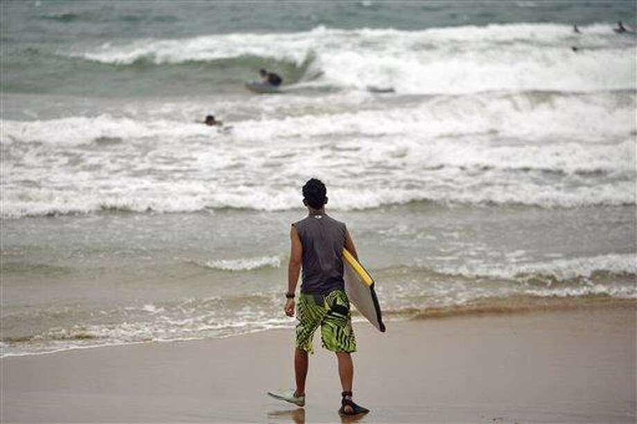 A surfer walks into the ocean as tropical storm Irene approaches to the island in Luquillo, Puerto Rico, Sunday, Aug. 21, 2011. The storm, packing winds of about 50 mph (85 kph) and tracking westward at 20 mph (32 kph), was expected to strengthen and pass near the U.S. island of Puerto Rico later Sunday or early Monday. (AP Photo/Ricardo Arduengo) Photo: AP / AP