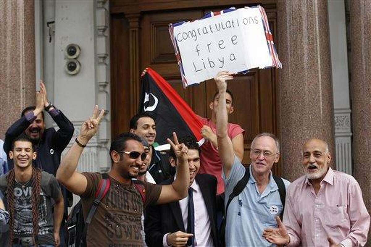 Libyans react to a man holding up a banner as they react to the situation in Libya outside the Libyan Embassy in London, Monday, Aug. 22, 2011. World leaders said Monday the end is near for Moammar Gadhafi's regime and began looking at Libya's future without the man who has held power there for 42 years. (AP Photo/Sang Tan)