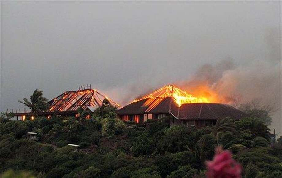In this image  issued  Monday Aug. 22, 2011 by Virgin Limited Edition shows British entrepreneur's  Sir Richard Branson's luxury home, on Necker Island, in the Caribbean, in flames as a fire which ripped through the luxury home. Guests including Academy Award-winning actress Kate Winslet escaped uninjured when fire destroyed Richard Branson's Caribbean home during a tropical storm Monday, said the British businessman. The Virgin Group boss said about 20 people, including Winslet and her children, were staying in the eight-bedroom Great House on Necker, his private isle in the British Virgin Islands. (AP Photo/Virgin Limited Edition/PA) UNITED KINGDOM OUT NO SALES NO ARCHIVE EDITORIAL USE ONLY Photo: AP /  Virgin Limited Edition PA