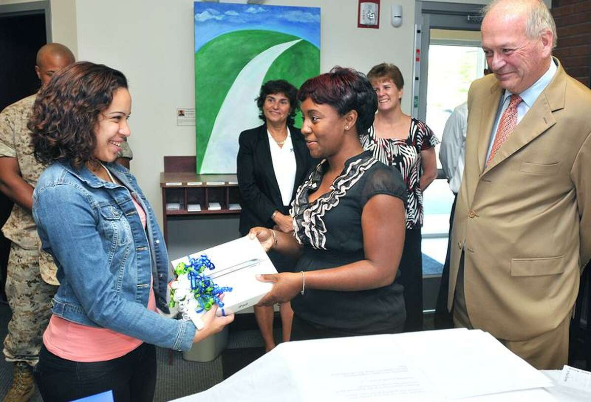 Samantha Ortiz, an 11th-grader at Cooperative Arts and Humanities High School, receives an iPad2 from Inesta Belardo, branch manager of Start Community Bank, as CEO William Placke looks on. Inesta received the prize as part of a financial capability initiative that reached over 500 youths enrolled in the Youth@Work summer jobs program. Peter Casolino/Register Cas110819 8/19/11