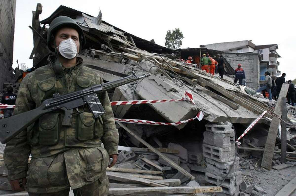 A Turkish soldier stands guard Monday as rescuers search for survivors in the debris of a building destroyed in Sunday's earthquake. Associated Press