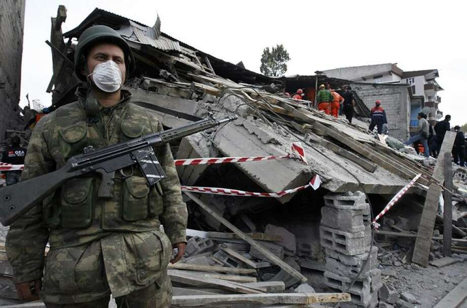 A Turkish soldier stands guard Monday as rescuers search for survivors in the debris of a building destroyed in Sunday's earthquake. Associated Press Photo: ASSOCIATED PRESS / AP2011