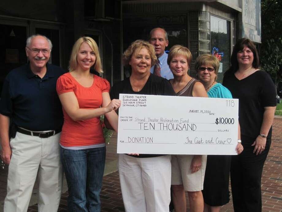 Shop owner Meghan Tarby, second from left, presents a $10,000 check to Seymour Culture and Arts Commission chairwoman Judy Simpson, third from left. Joining them are Seymour First Selectman Paul Roy, far left, Valerie D'Anna, fourth from left, Linda Bellavance, and Kathie Vrlik. Greater Valley Chamber of Commerce President William Purcell is in rear of photo.  Patricia Villers/Register