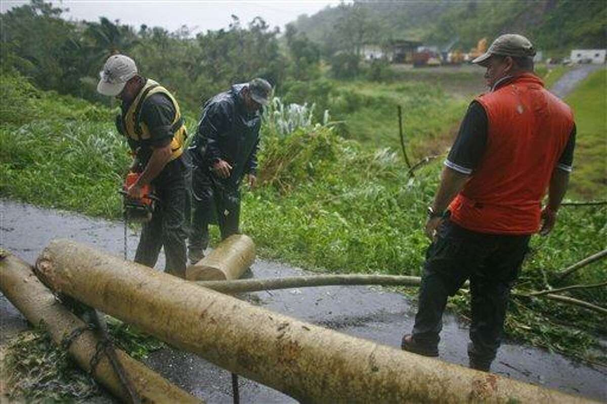Civil defense workers remove fallen trees from a road after hurricane Irene hit the area in Naguabo, Puerto Rico, Monday, Aug. 22, 2011. Hurricane Irene headed out over warm ocean water on a path that could take it to northeastern Dominican Republic and part of Haiti early Tuesday and to the U.S. mainland by the end of the week. (AP Photo/Ricardo Arduengo)