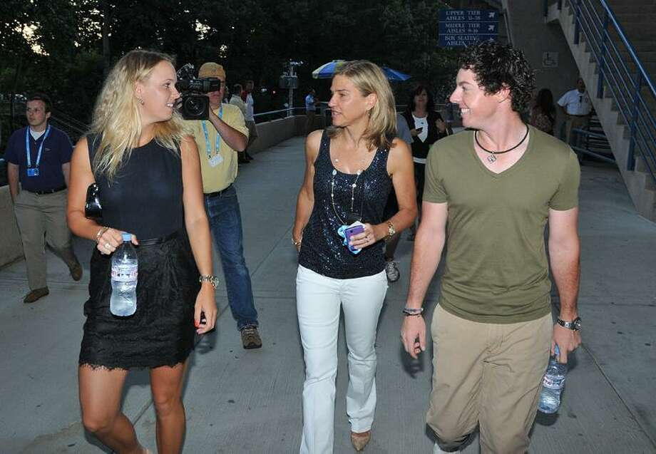 New Haven--US Open champion Rory McIlroy walks with Caroline Wozniacki, left, and Anne Worcester tournament director at the New Haven Open at Yale.  Photo-Peter Casolino/New Haven RegisterCas110822  8/22/11