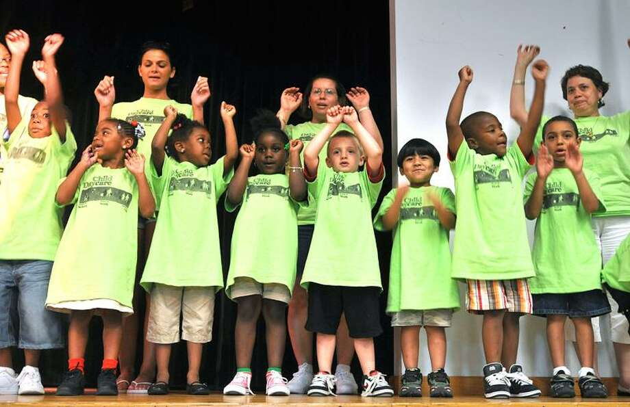 "Children from Sleeping Giant Day Care sing ""The Wheels on the Bus"" during the unveiling of the a new hydrogen-powered bus at Miller Library in Hamden Tuesday. Peter Casolino/Register"