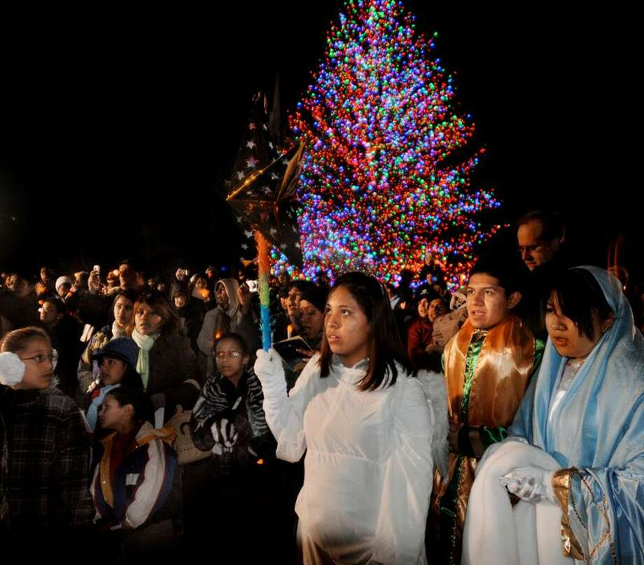 The Posada procession stops at a station on the New Haven Green Tuesday night. Posada is a popular Hispanic Christmas celebration that features biblical re-enactments. The event was  sponsored by the Knights of Columbus. Melanie Stengel/Register